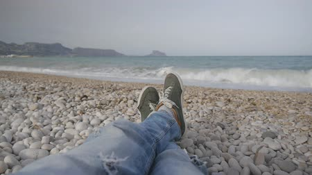 szakadt : Legs of a man in jeans and sneakers lying on a pebble beach against the sea during a storm Stock mozgókép
