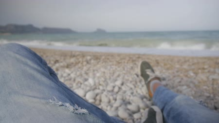 dechire : Male leg bent at knee in jeans and sneakers lying on a pebble beach against the sea during a storm