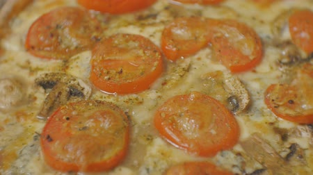 готовые к употреблению : Close-up pan shot of baked pizza with tomatoes and champignons