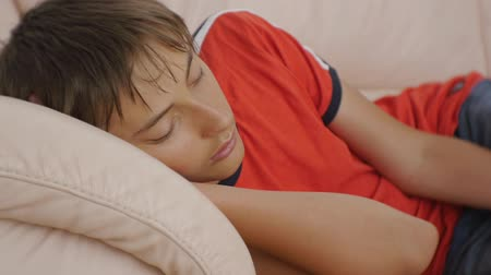 deprivation : Teenager sleeping on couch. Close-up of caucasian teen boy in red t-shirt and blue jeans sleeping on beige leather sofa in daytime. Lack of sleep