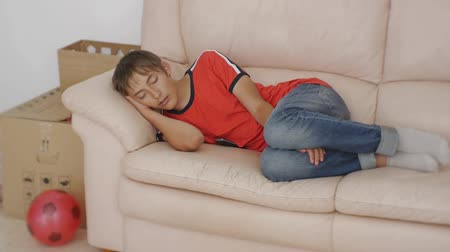 Teenager sleeping on couch. Caucasian teen boy in red t-shirt and blue jeans sleeping on beige leather sofa on moving boxes and soccer ball background. Moving to a new place concept