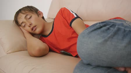 deprivation : Teenager sleeping on couch. Caucasian teen boy in red t-shirt and blue jeans sleeping on beige leather sofa in daytime. Lack of sleep