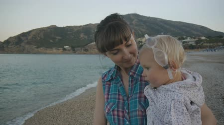 Smiling attractive caucasian woman in plaid blue shirt with baby girl with glasses for swimming walking on pebble beach along the sea