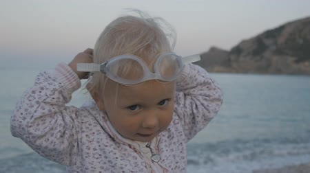 Portrait of mischievous caucasian blonde baby girl wearing glasses for swimming and looking at the sea