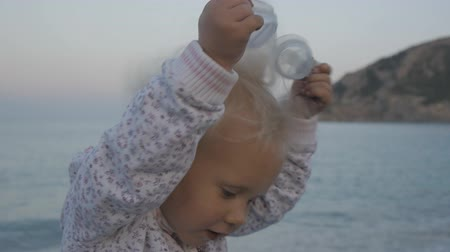 Portrait of mischievous caucasian blonde baby girl taking off swimming goggles on sea background Stok Video