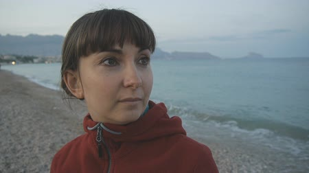 Young woman on empty beach background. Close-up of attractive caucasian brown haired female in red hoodie looking at the sea