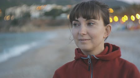 brisa : Young woman on evening beach background. Portrait of smiling caucasian brown haired female in red hoodie looking at the sea Stock Footage