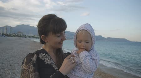 Young mother with baby on the sunset beach. Attractive caucasian woman in black tight dress walking with two years old child in her arms on empty pebble beach background. Concept of happy family Stok Video