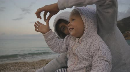 Teenager and child having fun on the beach. Closeup of two years old hooded baby and teen boy playing with pebbles on sunset sea background. Concept of happy family