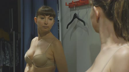 Young woman trying on clothes. Attractive caucasian female looks in the mirror turning around trying on beige bra in clothing stores fitting room