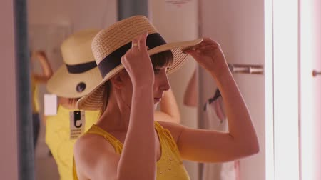 Young woman trying on clothes. Attractive caucasian female looks in the mirror turning her head trying on broad-brimmed straw hat in clothing stores fitting room