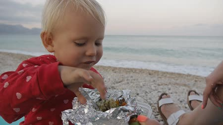Close-up of two years old baby eating a spoon with food from a foil tray on the beach. Child and mom on the sunset beach Stok Video