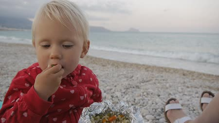 outing : Close-up of two years old baby eating green olive from a foil tray on the beach. Child and mom on the sunset beach