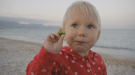 Close-up of two years old baby eating green olive and smiling on the seaside background
