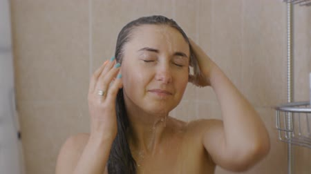 Woman taking a shower. Portrait of young smiling caucasian woman with closed eyes standing under the shower rinsing the hair on her head Stok Video