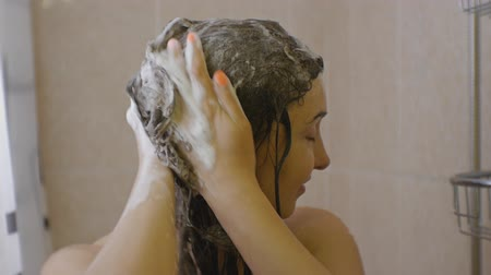 Woman taking a shower. Close-up of attractive caucasian woman soaps her hair applying shampoo foam