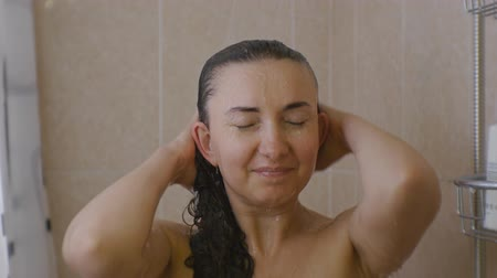 Woman taking a shower. Portrait of young caucasian woman with closed eyes standing under the shower rinsing the hair with water Stok Video