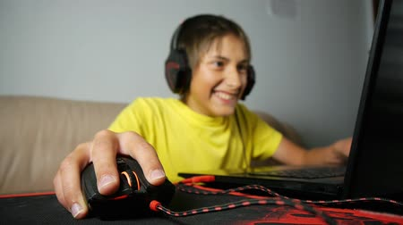 bağımlı : Teenager using laptop at night. Teen with headphones laughs using wired mouse on pad. Close-up of hand clicking computer gaming black and red mouse
