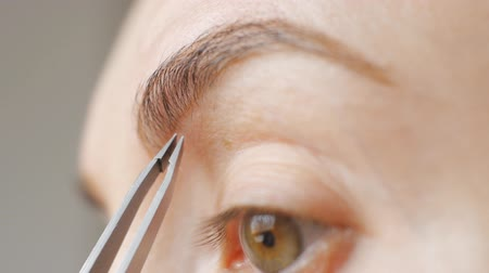 daily : Extreme close-up shot of face of young caucasian brown-eyed woman plucking eyebrows with tweezers