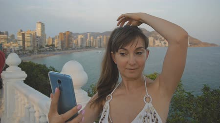 facetime : Attractive young woman taking selfie with smartphone. Caucasian girl making self portrait photo or video with cell phone on summer sunset seaside resort city background