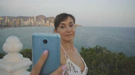 facetime : Attractive young woman taking selfie with smartphone. Smiling caucasian female making self portrait photo or video with cell phone on summer sunset seaside resort city background