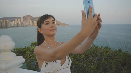 facetime : Attractive young woman taking selfie with smartphone. Cute smiling girl making self portrait photo or video with cell phone on summer sunset seaside resort city background