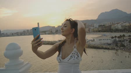 facetime : Attractive young female taking selfie with smartphone. Caucasian woman making self portrait photo or video with phone touching her hair on summer resort city mountain and sea landscape background