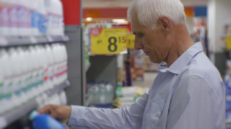 белить : Senior man in supermarket. Elderly gray-haired man in blue shirt choosing household chemicals on store shelves