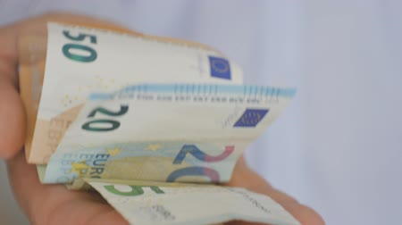 давать : Close-up of a hand of elderly man in a light blue shirt holding out euro notes