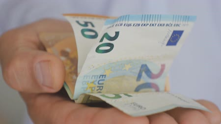 ücret : Close-up of a hand of mature man in a light blue shirt holding out euro notes
