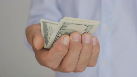 ücret : Close-up of a hand of elderly man in a light blue shirt holding out hundred-dollar bills Stok Video