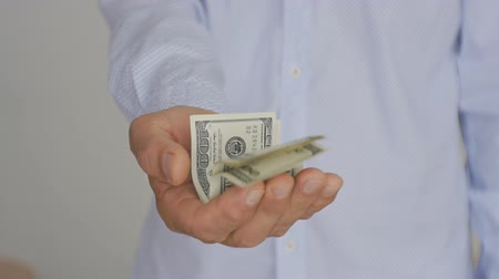 proponer : Close-up of a hand of mature man in a light blue shirt holding out hundred-dollar bills