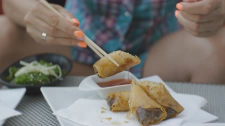meat rolls : Woman trying japanese cuisine. Close-up of attractive young caucasian woman taking with chopsticks and biting fried spring rolls with vegetables on open terrace of japanese restaurant