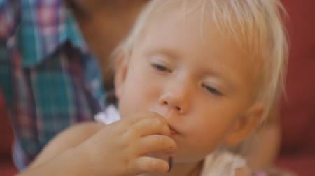 tempura : Woman with baby trying japanese cuisine. Close-up of blonde blue-eyed baby girl taking by hand and biting cabbage on open terrace of japanese restaurant
