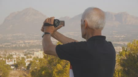 пенсия : Elderly male retired tourist. Active caucasian senior man stands on the hill filming sea coast and mountains on a portable video camera Стоковые видеозаписи