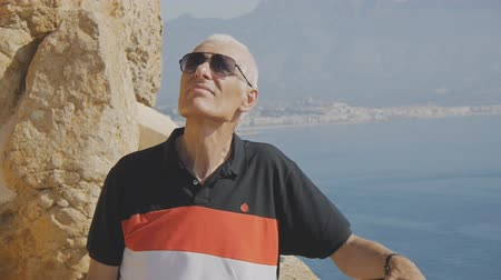 pensão : Elderly male retired tourist. Portrait of active caucasian gray-haired senior man in sunglasses looking up on sea coast background Vídeos