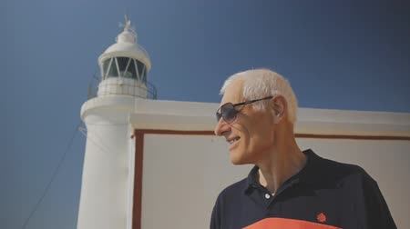 latarnia morska : Elderly male retired tourist. Happy active caucasian gray-haired senior man in sunglasses on white lighthouse and blue sky background Wideo