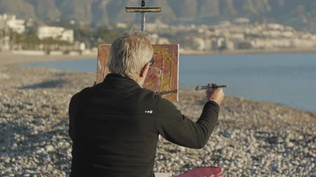akryl : Senior man paints a picture on the beach. Back view of elderly male artist painting abstract picture with a brush at pebble sunrise sea beach Dostupné videozáznamy