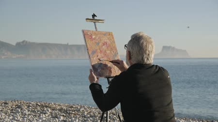 akryl : Senior man paints a picture on the beach. Back view of elderly male artist painting abstract picture with a spatula at pebble sunrise sea beach Dostupné videozáznamy
