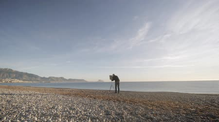 мольберт : Senior man paints a picture on the beach. Wide shot of elderly male artist sets the picture on the easel on the empty sea morning beach