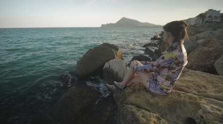 görüş uzaklığı : Young attractive woman sitting on rock stone looking into the distance on the sunset mountains and sea coast background Stok Video