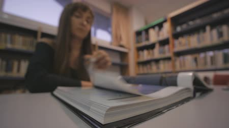 elszánt : Young caucasian woman turns the page of the illustrated book in library. Defocused shot Stock mozgókép