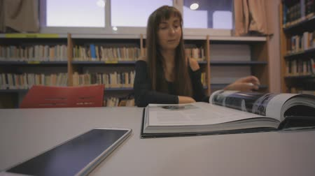 dedicado : Young caucasian woman turns the page of the illustrated book in library