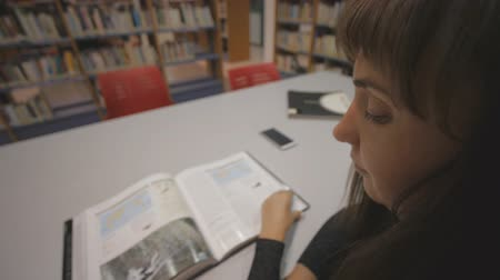 dedicado : Young caucasian woman leafing through an illustrated book in library. Over the shoulder shot