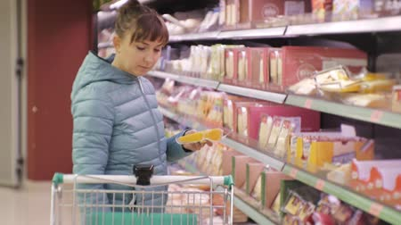 rokfor : Woman in supermarket. Young caucasian woman in blue jacket reading label of cheese putting it in the cart Stok Video