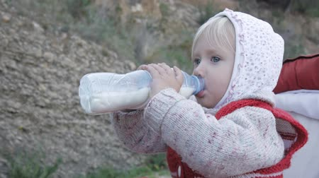 nyel : Child girl in hoodie and red knitted vest drinks milk or dairy drink from plastic bottle sittting in baby stroller in nature