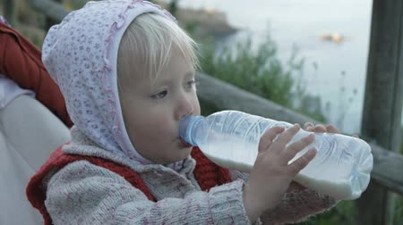 pletený : Child girl in hoodie and red knitted vest drinks milk or dairy drink from plastic bottle sittting in baby stroller on the background of the sea coast. Close up Dostupné videozáznamy