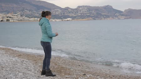 seixos : Woman at lonely cold beach. Caucasian woman throws stones into the calm sea