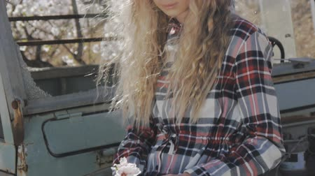 ピックアップ : Girl in blooming garden. Close-up of young caucasian girl in plaid dress holding almond flower in hand sitting on abandoned pickup trucks fender. Slow motion 動画素材