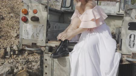 ピックアップ : Woman in blooming garden. Attractive blonde woman in white skirt and black shoes tying shoelaces sitting in back of abandoned pickup truck near almond blossom trees